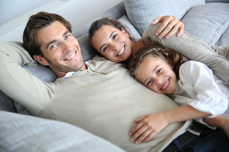 Pais com a menina que encontra-se no sofá que sente hapy imagens de stock royalty free