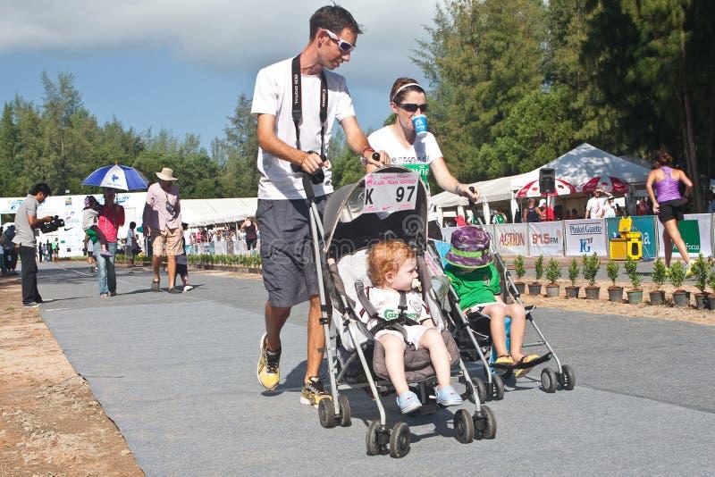 Pais com os bebês no pushchair que começa a raça foto de stock