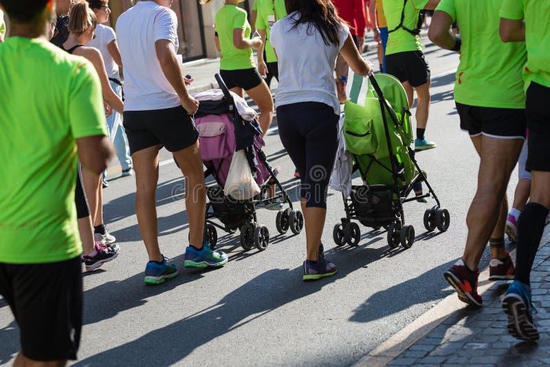 Pais com os Pushchairs para crianças em um evento da raça de maratona da cidade imagens de stock