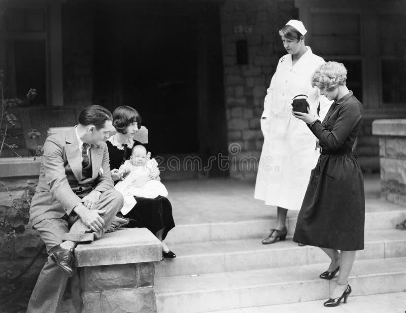 Pais com seu bebê novo na frente do hospital que está sendo fotografado (todas as pessoas descritas não são umas vivas mais longo fotografia de stock