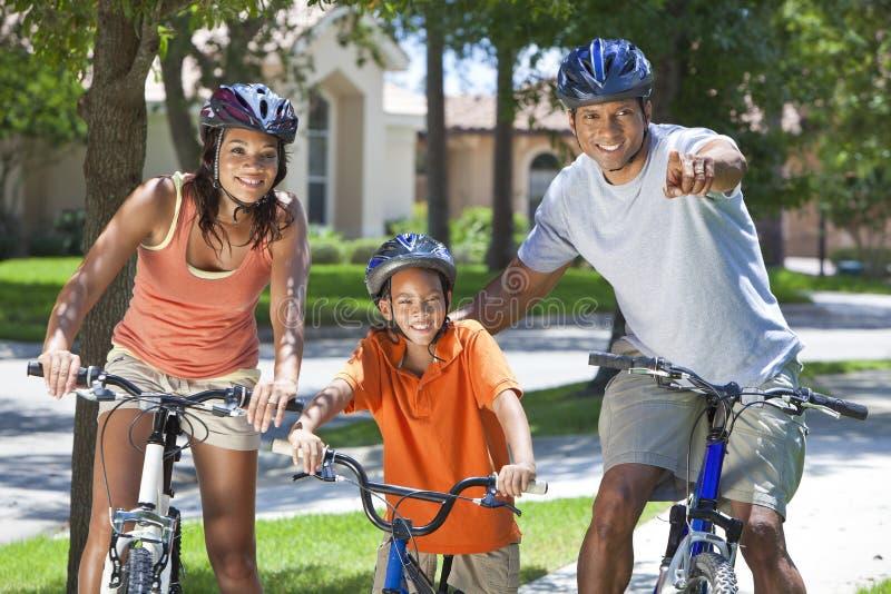 Pais do americano africano com a bicicleta da equitação do filho do menino imagens de stock royalty free