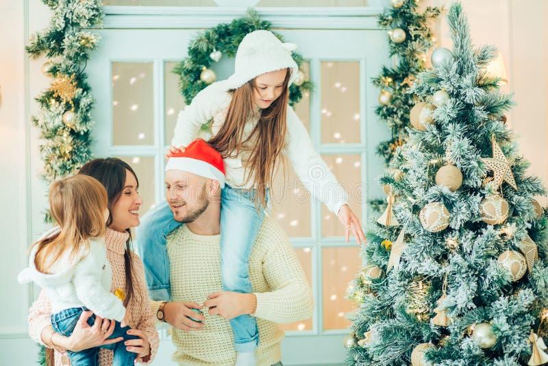 Pais e bebê que têm o divertimento perto da árvore de Natal Família loving pela árvore de Natal foto de stock royalty free