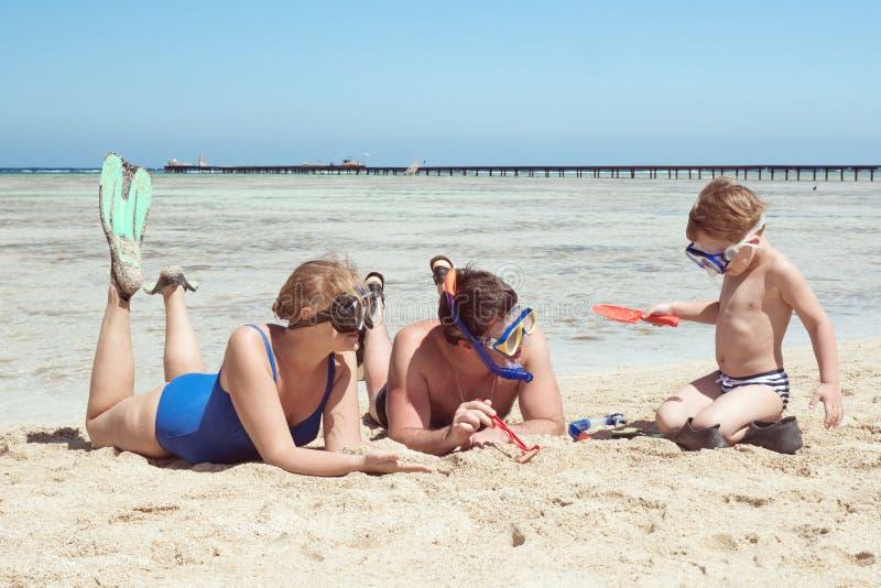Pais e criança nos tubos de respiração que jogam na praia imagem de stock royalty free