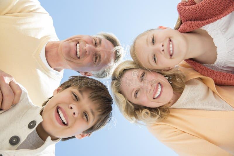 Pais e crianças alegres contra o céu azul claro fotos de stock
