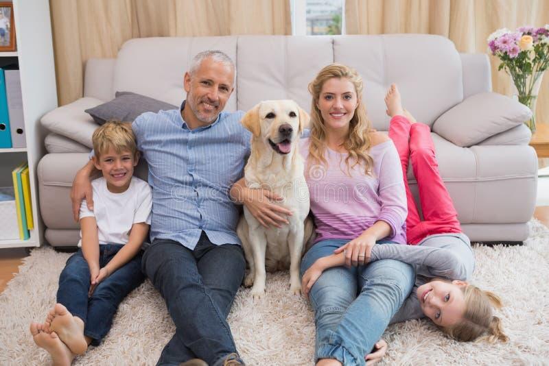 Pais e crianças no tapete com Labrador foto de stock