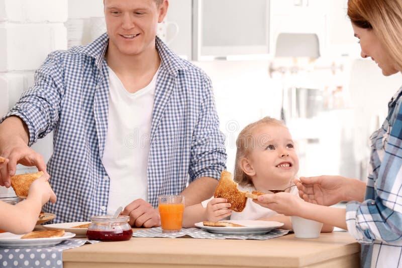 Pais e crianças pequenas bonitos que comem o café da manhã fotografia de stock royalty free