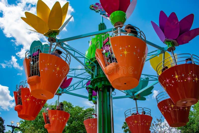 Pais e crian?as que apreciam potenci?metros de flor coloridos a bordo da torre da flor de Abby's em Seaworld na ?rea internaciona foto de stock