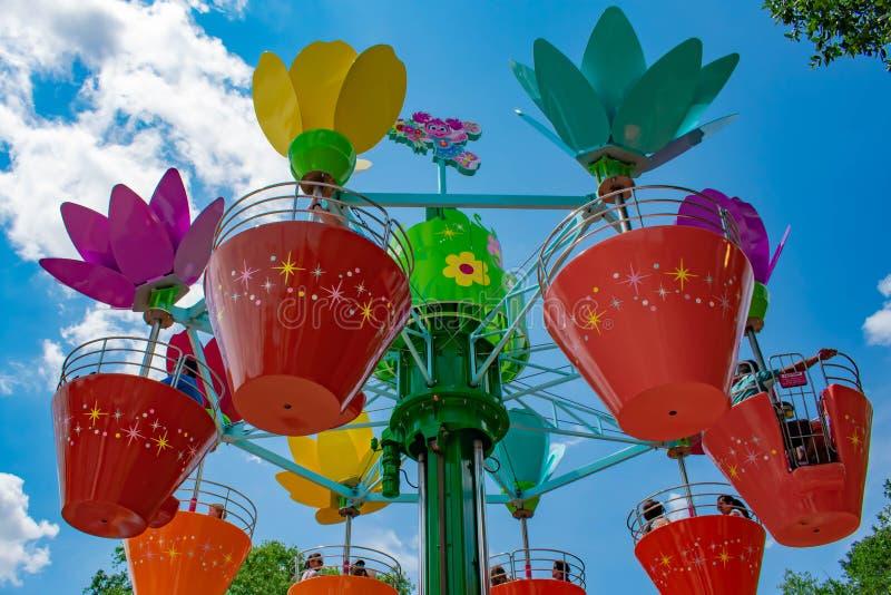 Pais e crian?as que apreciam potenci?metros de flor coloridos a bordo da torre da flor de Abby's em Seaworld na ?rea internaciona fotos de stock