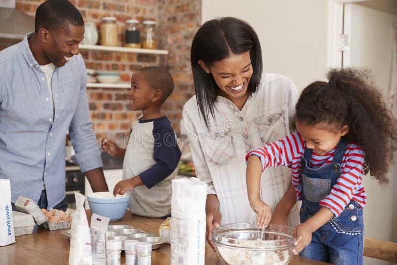 Pais e crianças que cozem bolos na cozinha junto foto de stock