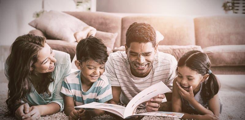 Pais e crianças que encontram-se no tapete e no livro de leitura na sala de visitas foto de stock royalty free