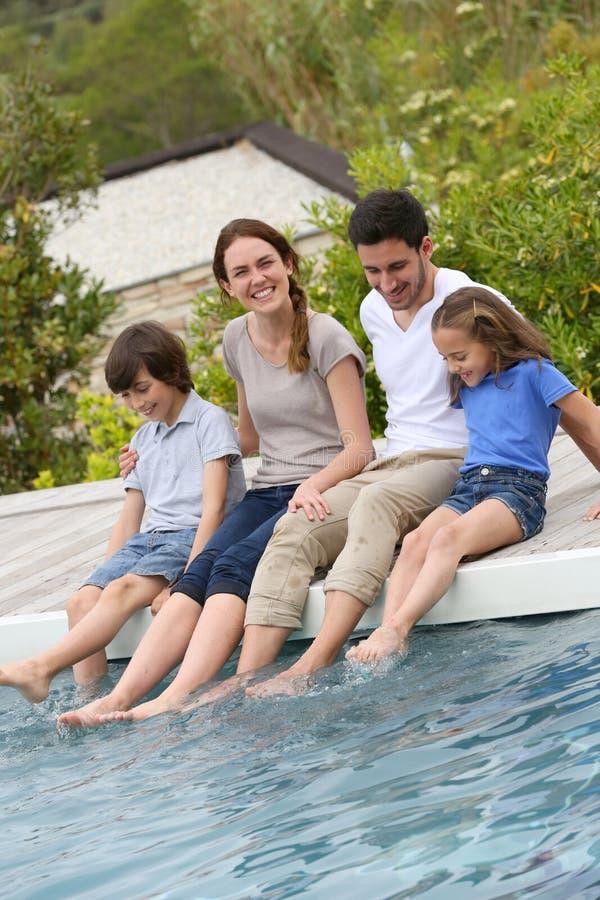 Pais e crianças que põem os pés na piscina imagens de stock