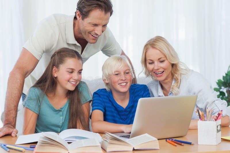 Pais e crianças que usam um computador fotografia de stock