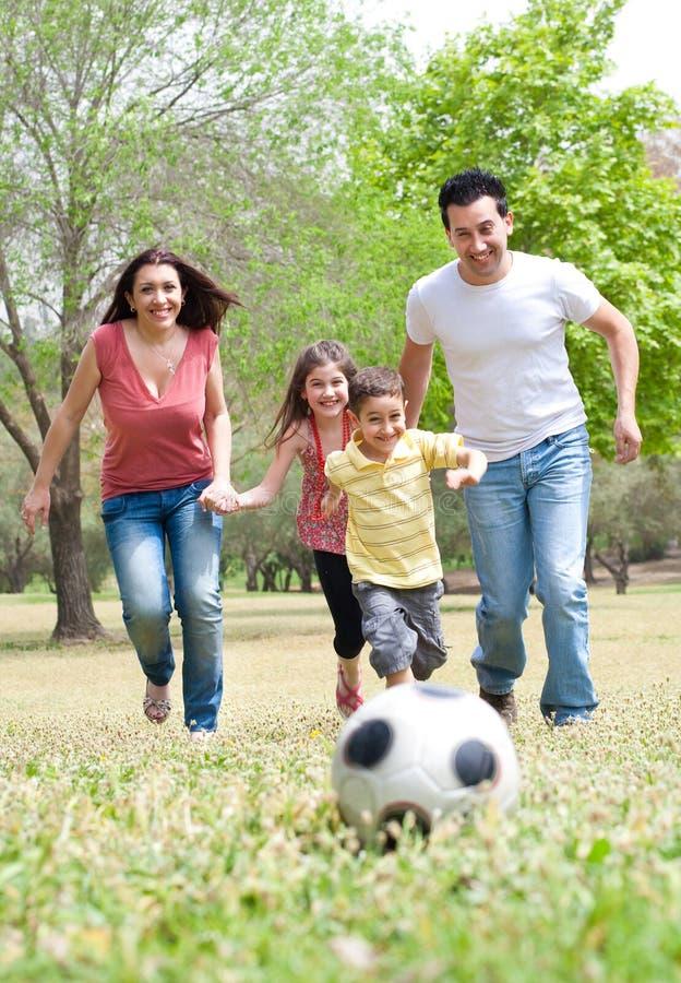 Pais e duas crianças novas que jogam o futebol imagens de stock royalty free
