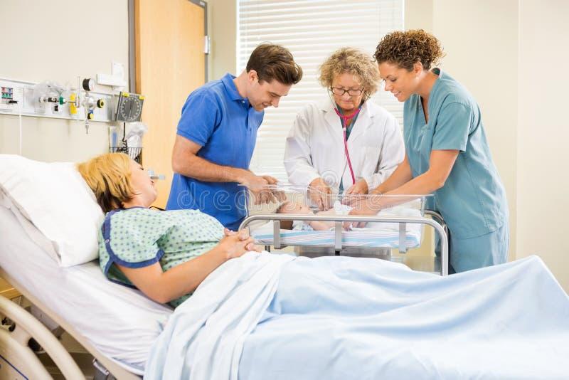 Pais e enfermeira do doutor Examining Baby While fotos de stock