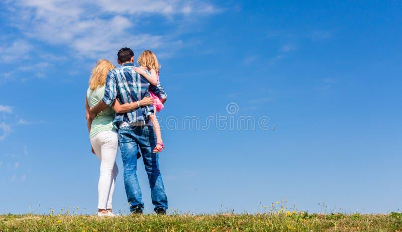 Pais e filha, braço no braço na vista traseira foto de stock