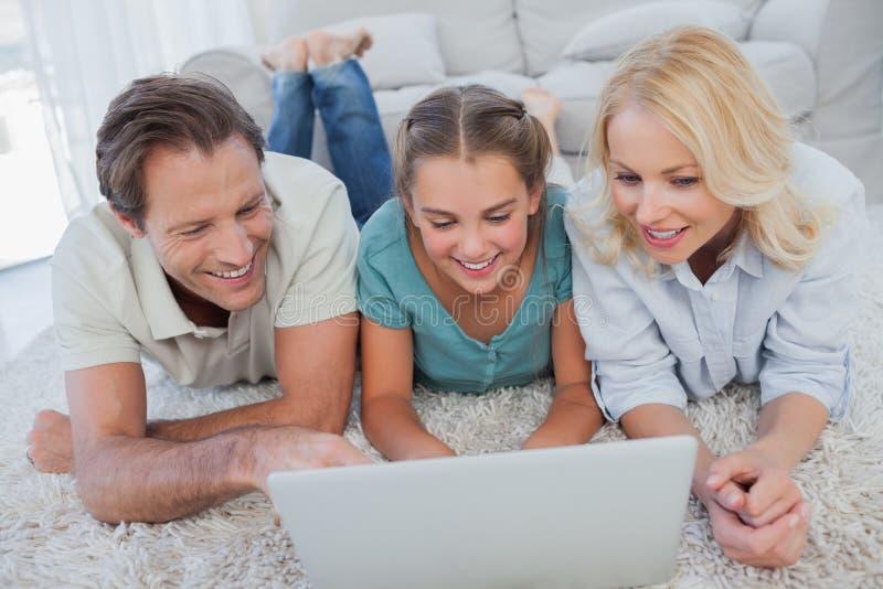 Pais e filha felizes que usa um portátil foto de stock