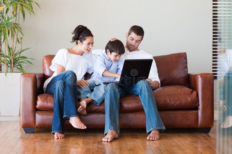 Pais e filho que jogam com um portátil fotografia de stock royalty free