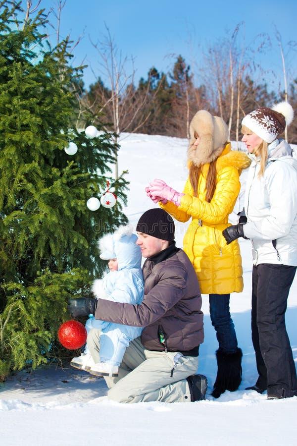 Pais e miúdos que decoram a árvore de Natal imagens de stock royalty free