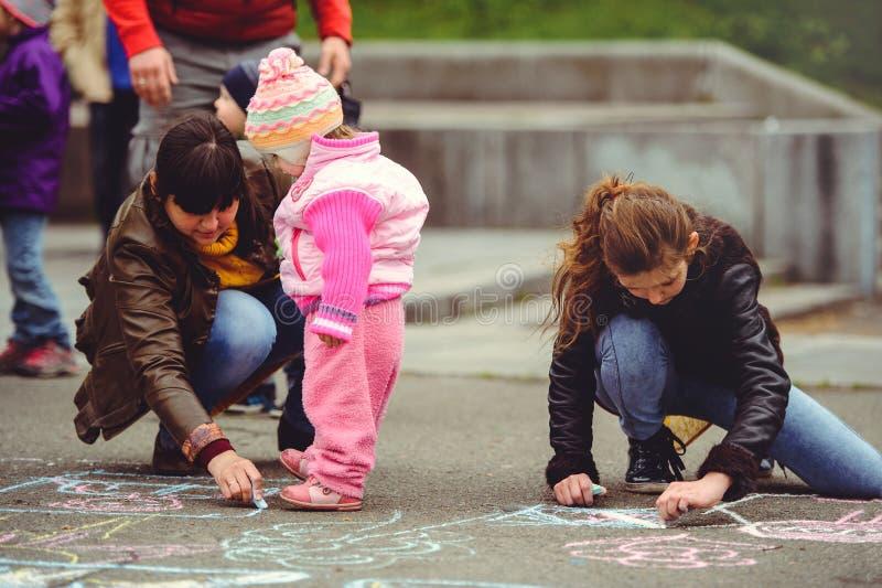 Pais e pintura das crianças no asfalto foto de stock royalty free
