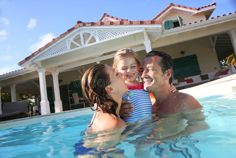 Pais e sua criança que jogam na piscina fotos de stock royalty free