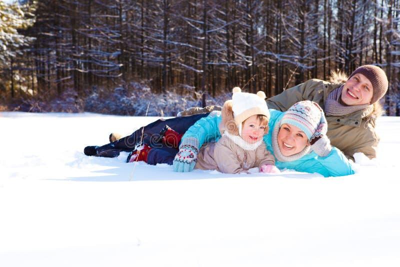 Pais e sua filha que encontram-se na neve imagem de stock royalty free