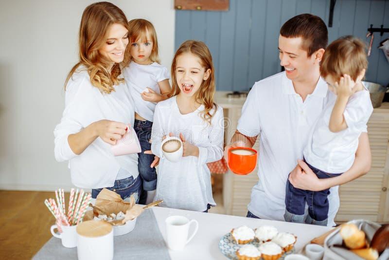 Pais e suas três crianças que comem na cozinha e que apreciam junto fotografia de stock