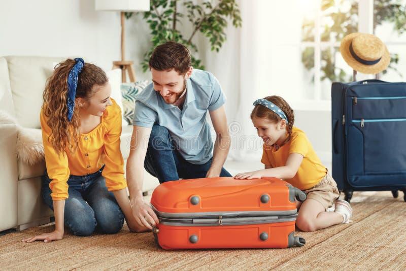 Pais felizes com filha com mala saindo para viagem foto de stock