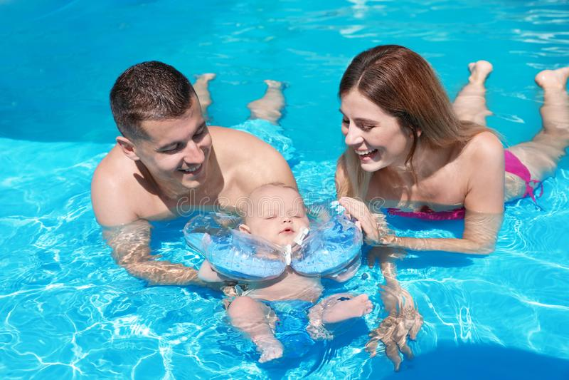 Pais felizes com o bebê pequeno na piscina fotos de stock