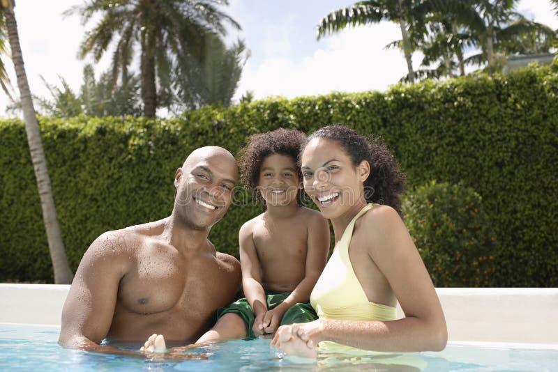 Pais felizes com o filho na piscina foto de stock royalty free