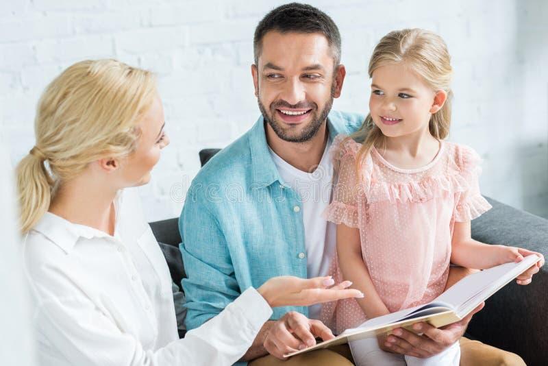 pais felizes com o livro de leitura pequeno bonito da filha junto imagens de stock