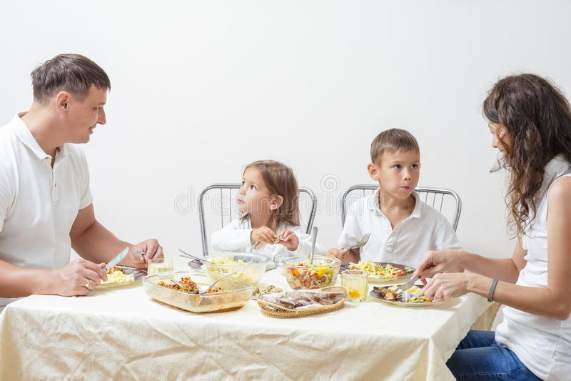 Pais felizes com suas crianças que comem o café da manhã em casa foto de stock