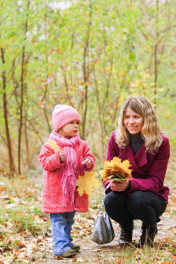 Pais felizes com uma criança que joga na natureza do outono no parque imagem de stock