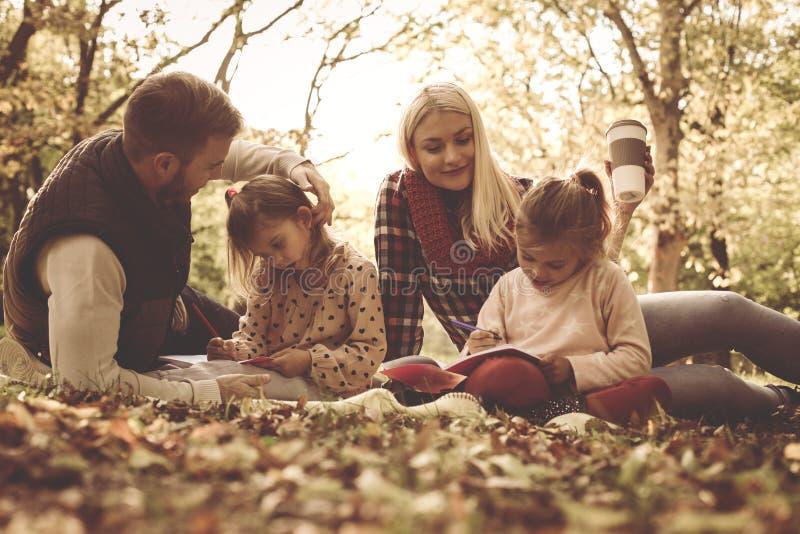 Pais felizes de sorriso com a filha no parque foto de stock royalty free