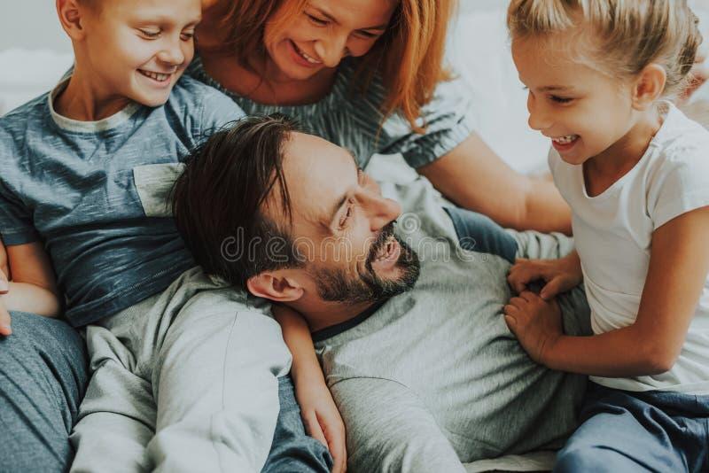 Pais felizes e duas crianças que têm o divertimento junto foto de stock