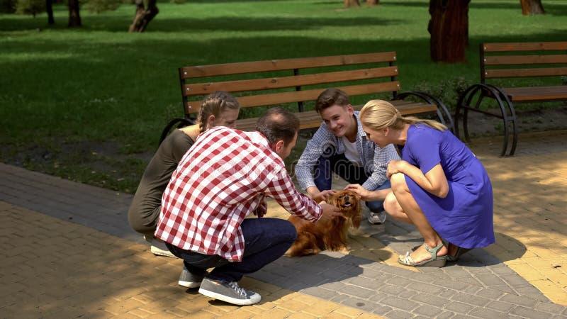 Pais felizes e suas crianças que afagam o cão bonito no parque, adoção do animal de estimação imagens de stock