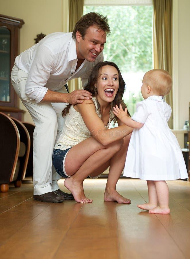 Pais felizes que ajudam o bebê a tomar primeiras etapas imagem de stock