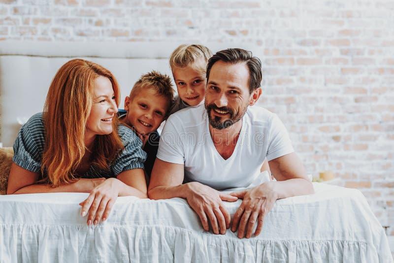 Pais felizes que colocam na cama com crianças fotografia de stock royalty free