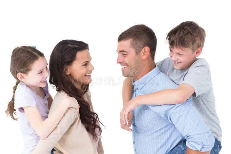 Pais felizes que dão às cavalitas o passeio às crianças fotografia de stock