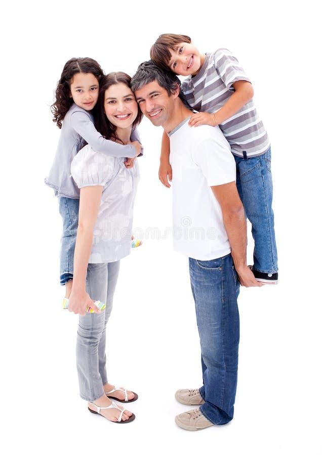 Pais felizes que dão a suas crianças um sobreposto fotografia de stock