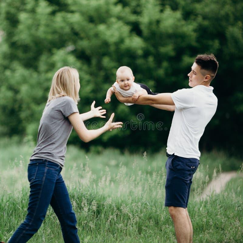 Pais felizes que jogam com filha do bebê fora fotos de stock