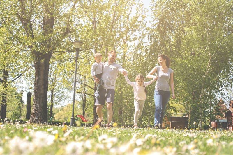 Pais felizes que jogam com suas crianças no prado imagens de stock royalty free