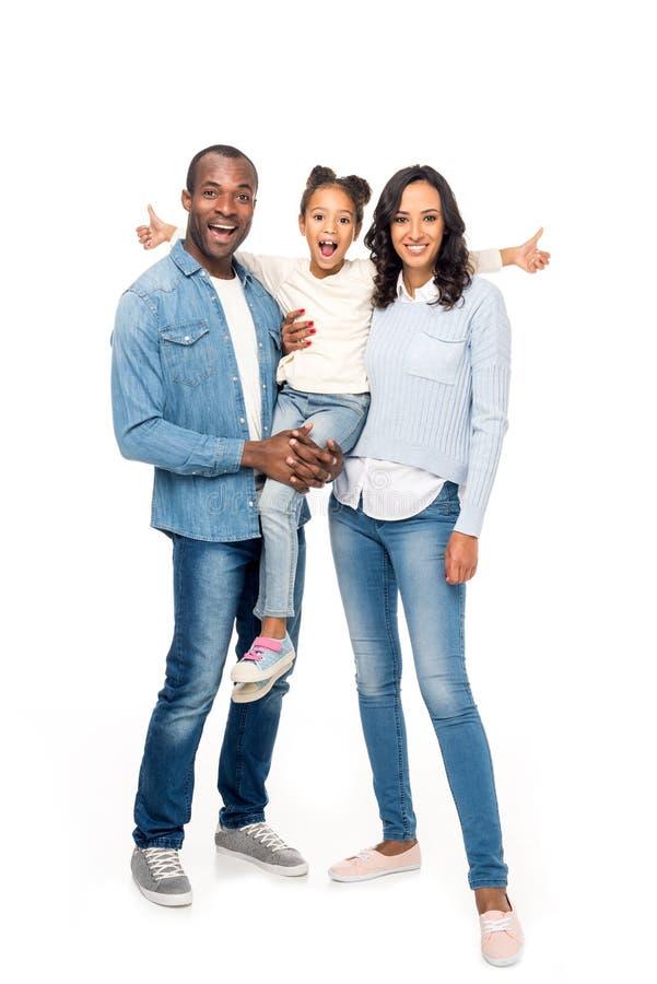 pais felizes que levam a menina afro-americano bonito que mostra os polegares acima imagens de stock royalty free