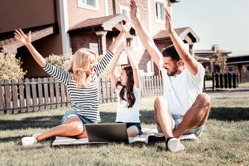 Pais felizes surpreendidos que passam o tempo com filha e que exultam fotografia de stock royalty free
