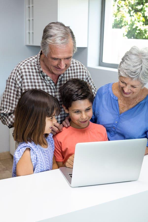 Pais grandes e netos que interagem usando o portátil imagens de stock royalty free