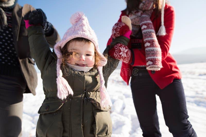 Pais irreconhecíveis com sua filha em uma caminhada no inverno fotografia de stock