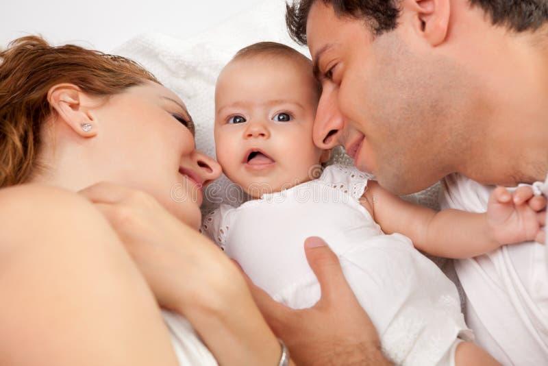 Pais Loving com sua menina bonito na cama fotografia de stock