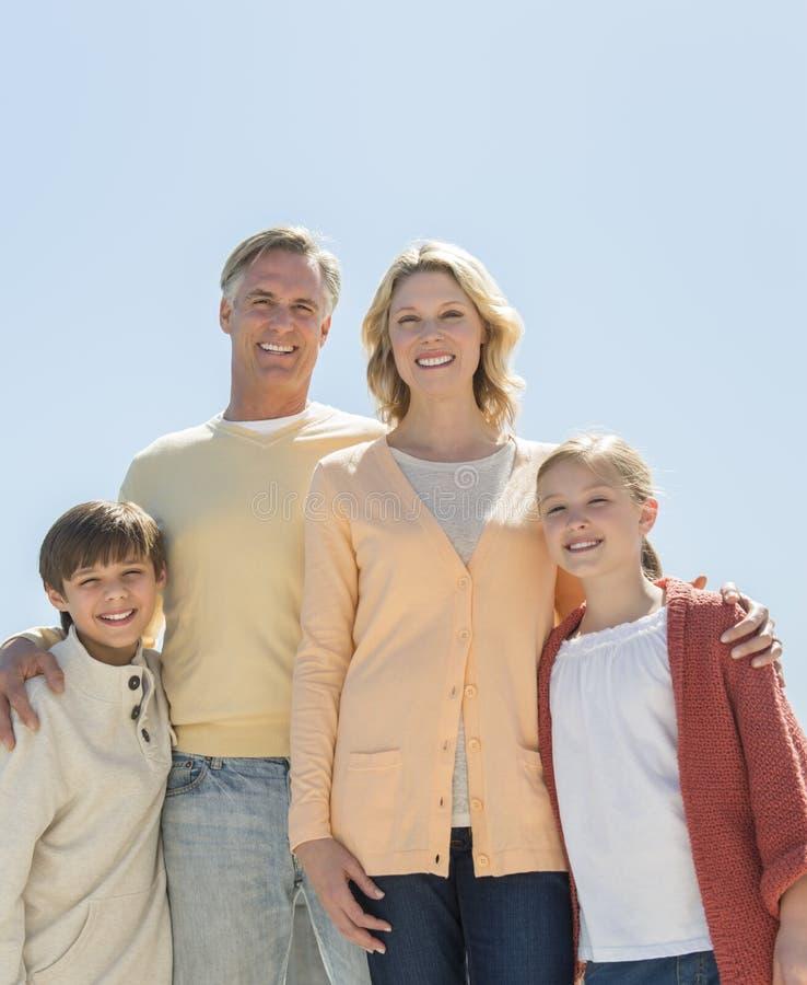 Pais loving e crianças que estão contra o céu azul claro imagens de stock royalty free