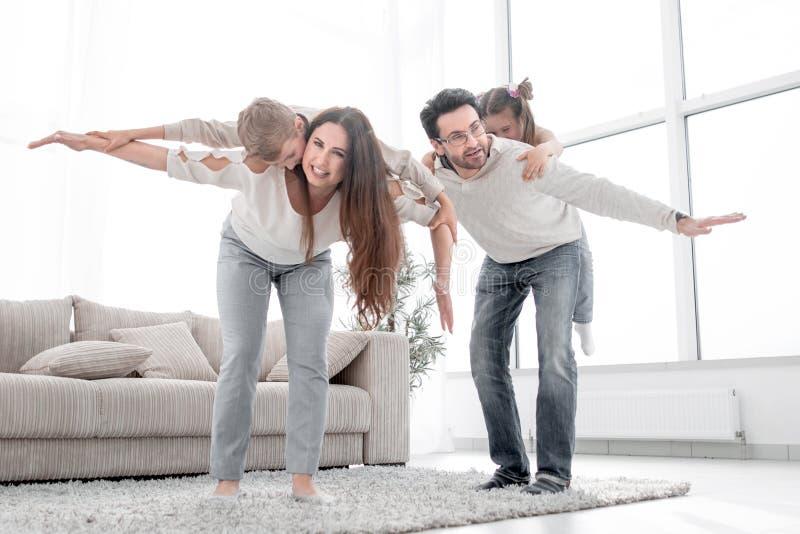 Pais loving que jogam com as crianças em sua casa imagem de stock royalty free
