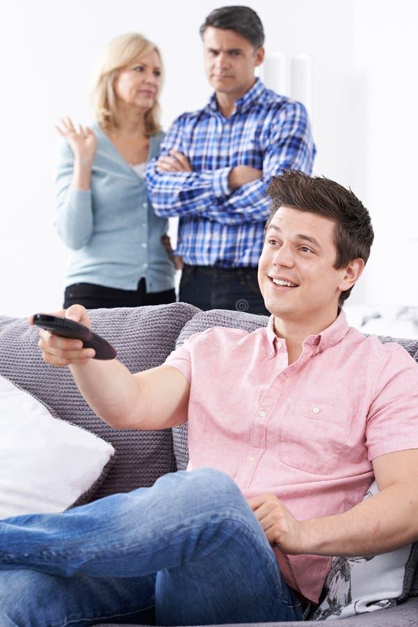 Pais maduros frustrados com o filho adulto que vive em casa fotos de stock