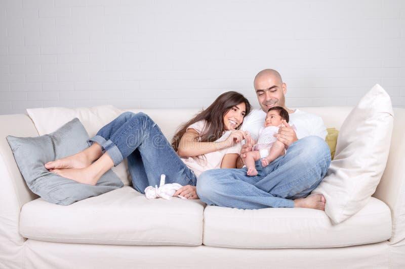 Pais novos com bebê pequeno em casa imagens de stock royalty free